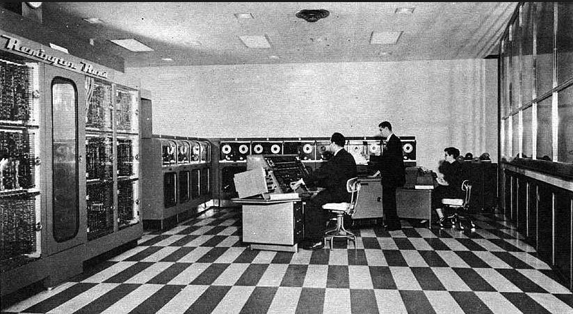 Vista general de la instalación del UNIVAC  A la izquierda tenemos a Mauchly a los mandos del UNIVAC junto a dos operarios de la máquina.